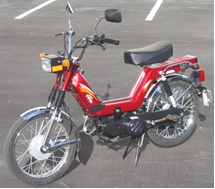 A red moped sitting on a paved driveway